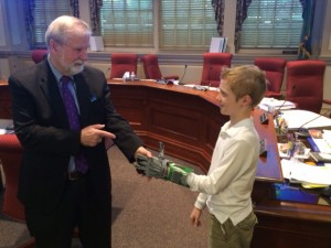 Colin Consavage shows Senator McDowell the prosthetic hand he made for himself using the 3D printer at the Wilmington Library